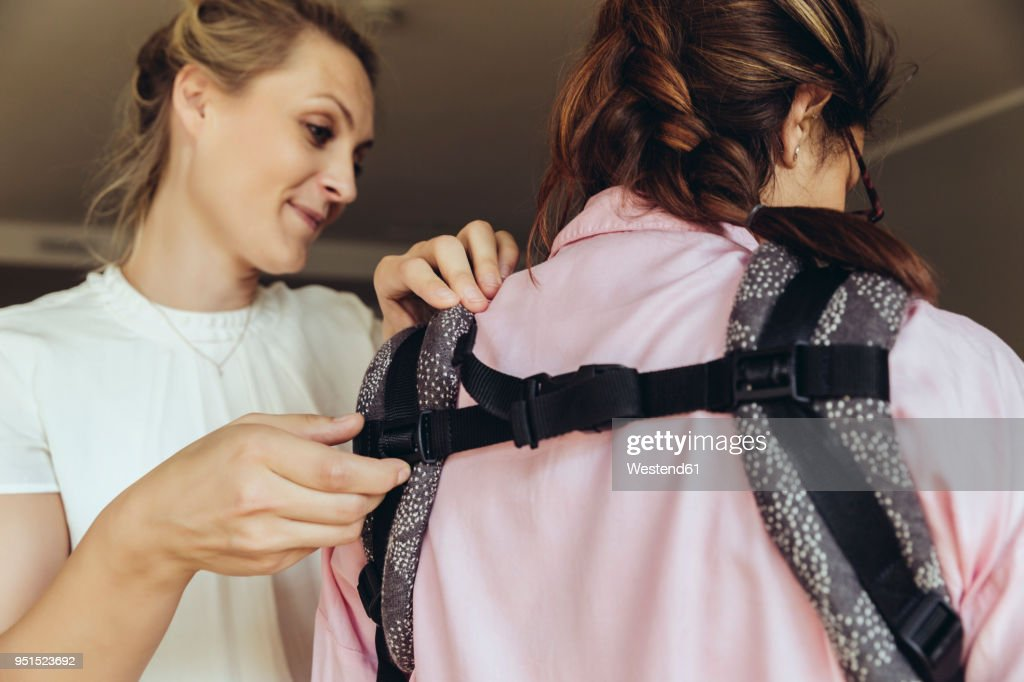 Midwife showing young mother how to fasten a baby sling : Stock Photo