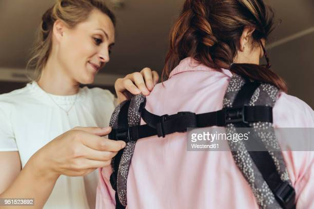 Midwife showing young mother how to fasten a baby sling