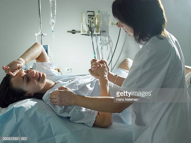 Midwife supporting woman during pregnancy in hospital