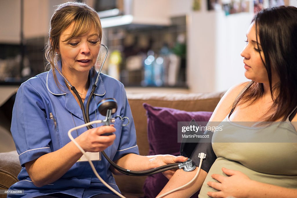 Midwife takes patients blood pressure on home visit : Stock Photo