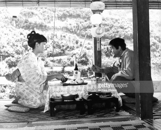 Mie Hama in a kimono entertaining Sean Connery as they eat traditional Japanese cuisine in a scene from the film 'You Only Live Twice' 1967