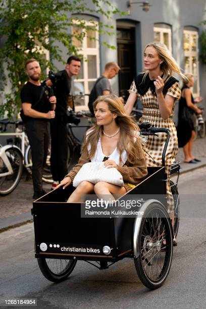 Mie Juel wearing knitted brown dress, white bag and Marie Hindkær wearing withe and brown checked dress in a Christiania bike outside Ganni during...