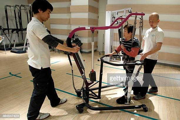 Mieko Kawakami who suffers from gait disorder due to partial paralysis center walks with an assistive walking device after being fitted with...