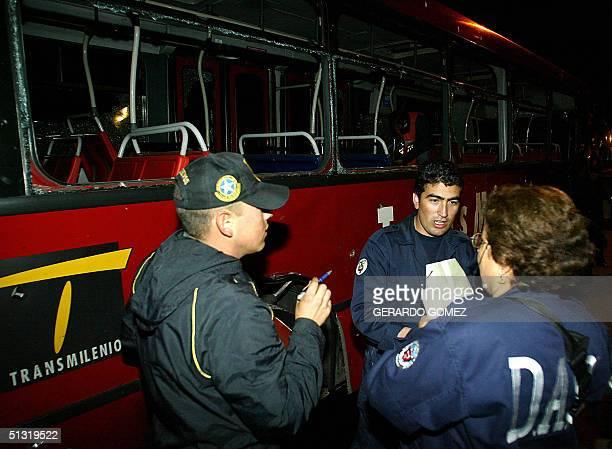 Miembros de la Policia Secreta inspeccionan los danos ocacionados por la explosion de una bomba de bajo poder a un autobus de la compania...