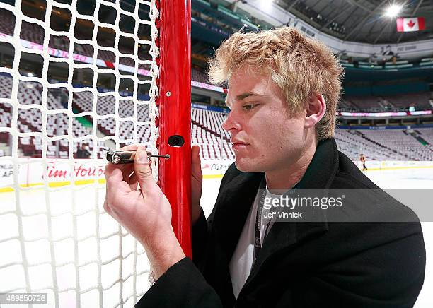Miesen with NHL Arena Technical Operations adjusts one of the new in goal video review cameras situated in the post of the goal net before Game One...