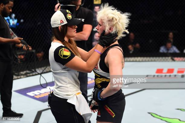 Miesha Tate greets Cindy Dandois of Belgium after her fight against Alexis Davis in their women's bantamweight bout during the UFC Fight Night event...