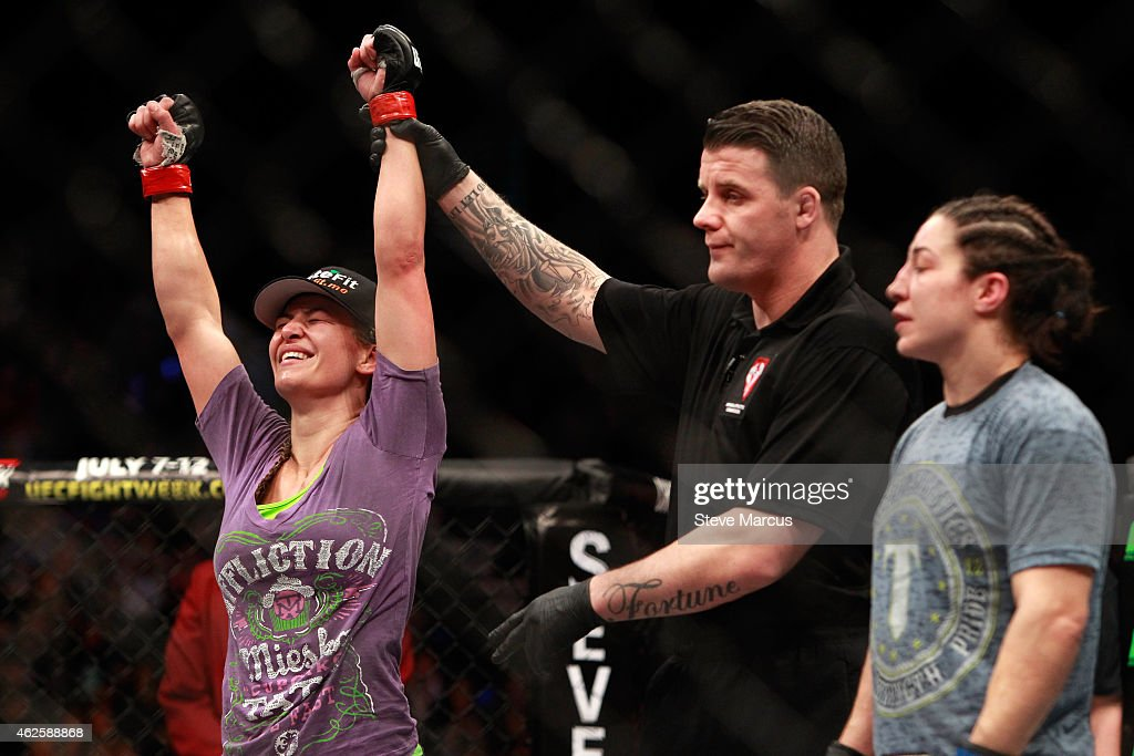 Miesha Tate (L) is declared the winner over Sara McMann in their bantamweight bout during UFC 183 at the MGM Grand Garden Arena on January 31, 2015 in Las Vegas, Nevada. Tate won the fight by majority decision.