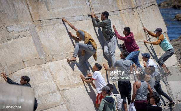 Migants climb a sea wall in the northern town of Fnideq after attempting to cross the border from Morocco to Spain's North African enclave of Ceuta...