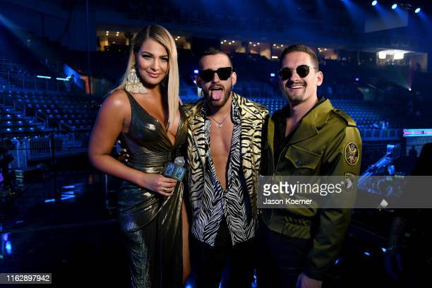 MIgbelis Castellano and Mau Montaner and Ricky Montaner from Mau and Ricky speak on stage during Premios Juventud 2019 at Watsco Center on July 18...