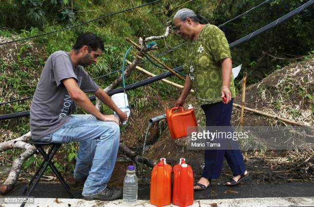 Migdalia Aceuedo and her son Mathews Rosado Aceuedo collect spring water for their house by a downed power line nearly three weeks after Hurricane...