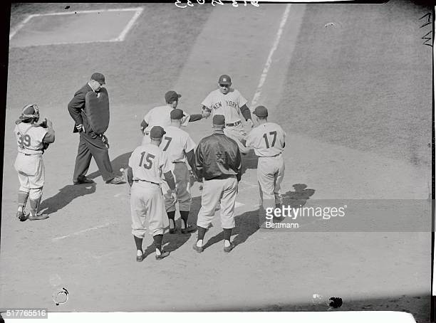 Mighty Yogi Berra of the Yankees is shown being welcomed home after his Homeric clout with bases loaded in the second inning of the second World...