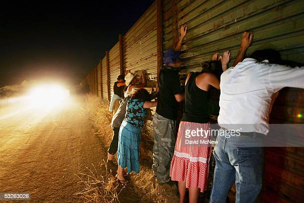 Migrant activists protesting nightly patrols by citizen volunteers who search for people crossing USMexico border lean against the border fence to...