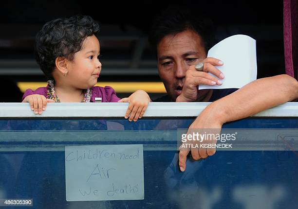 A migrant and a young girl get fresh air from a window where a placard calling for help and reading children need air we death's has been placed at a...