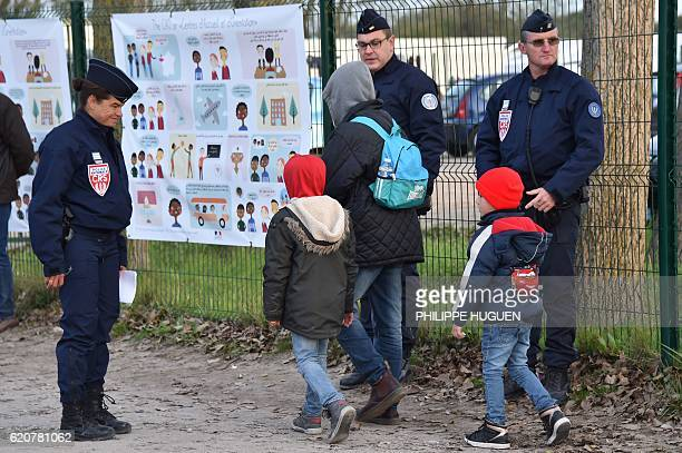 A migrant and children walk past French policemen to climb in busses as they leave the 'Jules Ferry' reception centre next to the recently demolished...