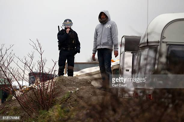 A migrant and police officer look on as police and demolition workers clear the 'jungle' migrant camp on March 01 2016 in Calais France Police and...