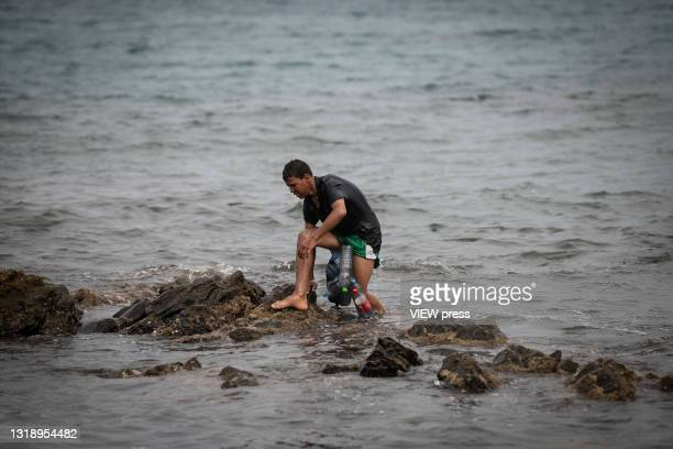 Migrant arrives at Tarajal beach after having crossed the border between Morocco and Spain swimming on May 19, 2021 in Ceuta, Spain. After a...