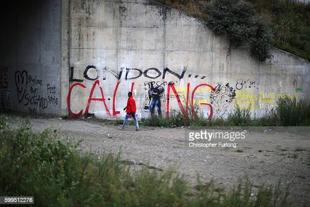 A migrant at the Jungle camp walks past graffiti as local farmers truckers and business owners protest and block the A16 motorway on September 5 2016...