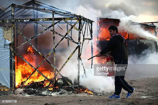 A migrant attempts to extinguish a fire in a burning hut as police officers clear part of the 'jungle' migrant camp on February 29 2016 in Calais...