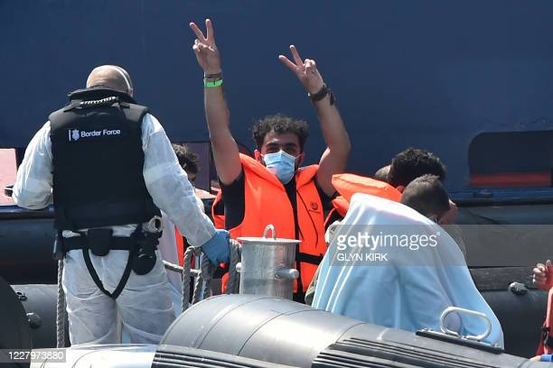 A migrant believed to have been with a group picked up from boats in the Channel gestures to photographers from Coastal patrol vessel HMC Speedwell...