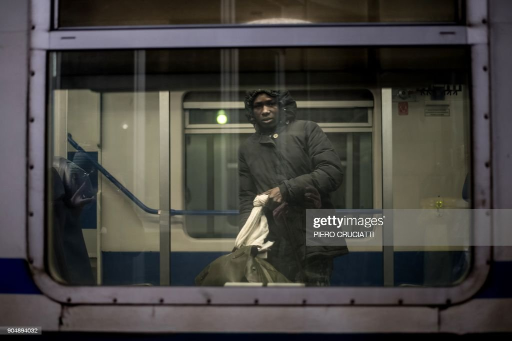 A migrant boards a train back to Turin, after giving up the attempt to cross the border between Italy and France, in Bardonecchia on January 13, 2018. Migrants are now trying to reach France crossing the Italian Alps by the snow-covered pass Colle della Scala (Col de l'Echelle) despite snow and bad weather conditions. / AFP PHOTO / Piero CRUCIATTI