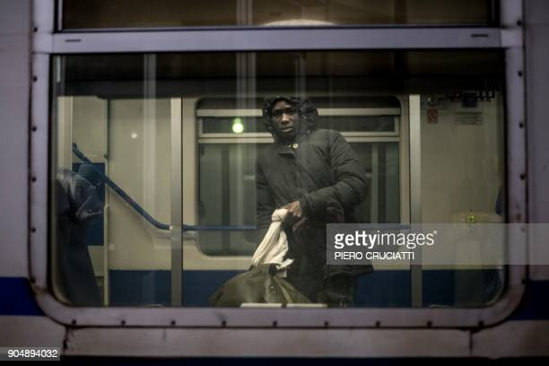 A migrant boards a train back to Turin after giving up the attempt to cross the border between Italy and France in Bardonecchia on January 13 2018...