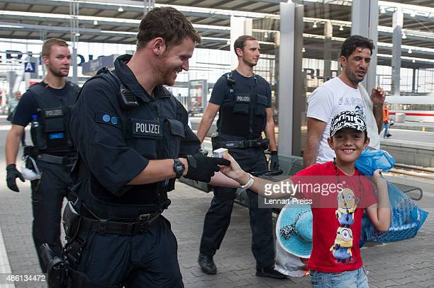 A migrant boy hands over a pack of glucose to a policeman as police detain migrants who arrived at Munich Hauptbahnhof main railway station without...