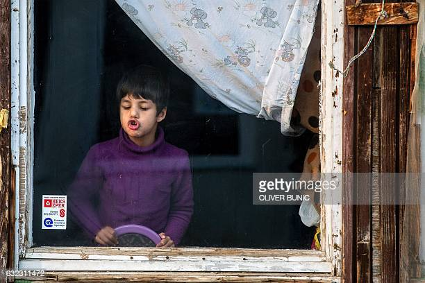 A migrant boy plays at a window in a refugee camp near Belgrade on January 21 2017 According to the latest figures around 7000 migrants are stranded...