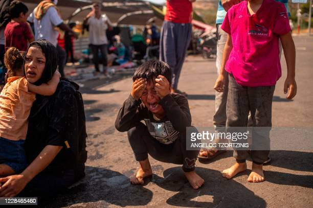 Migrant boy reacts after police threw tear gas during clashes near the city Mytilene on the Greek island of Lesbos, on September 12 a few days after...