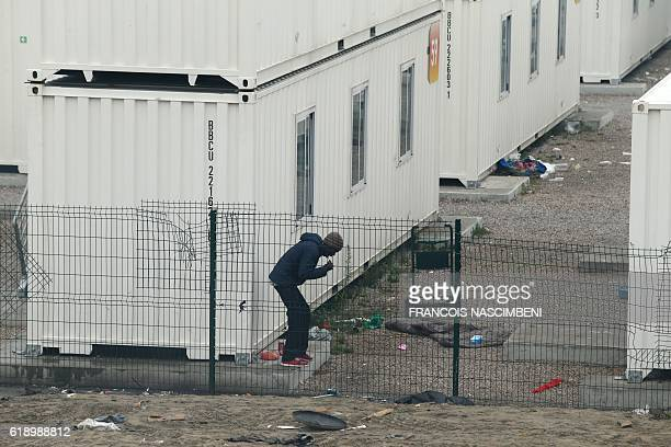 A migrant brushe his teeth at the temporary reception centre housing minors in the Jungle migrant camp in Calais northern France on October 29 during...