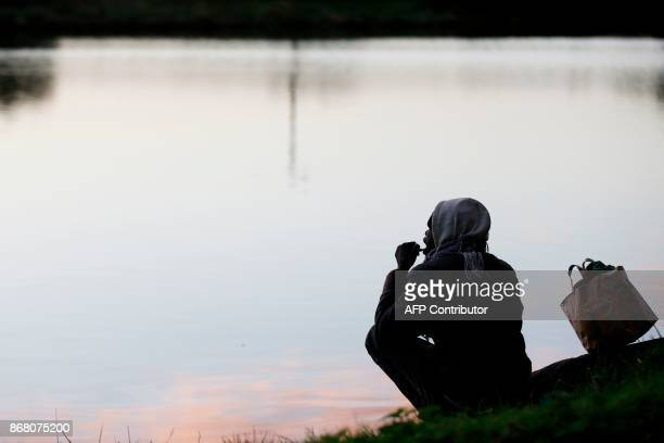 A migrant brushes his teeth beside a body of water near the port of Ouistreham near Caen northwestern France on October 30 2017 Migration is a big...