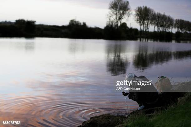 TOPSHOT A migrant brushes his teeth beside a body of water near the port of Ouistreham near Caen northwestern France on October 30 2017 Migration is...