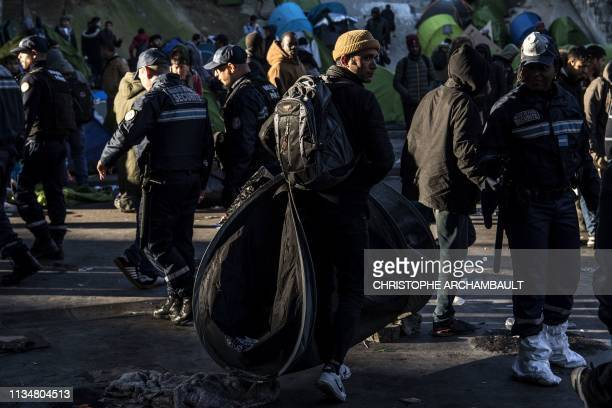 A migrant carries a tent as police officers and security agents carry out an evacuation of a makeshift camp at Porte de la Chapelle in the north of...