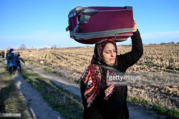Migrant carries her belongings walking towards greece border on February 28 , 2020 near Turkey-Greece border near Pazarkule border gate in Edirne. -...