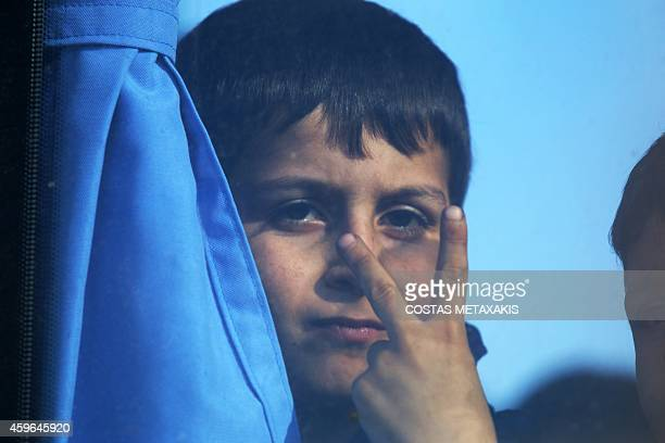 A migrant child gestures on November 27 2014 upon his arrival in the Cretan port of Ierapetra Around 700 migrants aboard a freighter that had been...