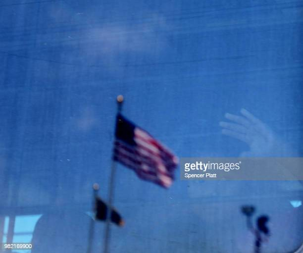 A migrant child looks out the window of a bus as protesters try to block a bus carrying migrant children out of a US Customs and Border Protection...