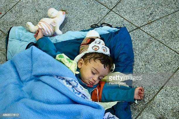 Migrant child sleeps inside Keleti Station on 05 September 2015 in Budapest Hungary Last night the Hungarian government ordered a fleet of buses to...