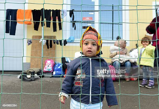 A migrant child stands behind a fence waiting for the transport to the AustrianGerman border near the village Kollerschlag Upper Austria on October...