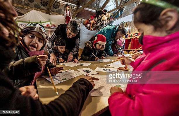 Migrant children attend a lesson in a makeshift school on February 10 in the socalled 'Jungle' migrant camp in Calais Inaugurated early February the...