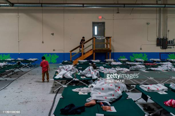 Migrant children from different Latin American stand near rows of cots inside the Casa del Refugiado or The House of Refugee a new centre opened by...