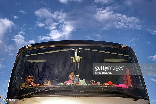Migrant children look from the window of a bus in Pireaus, port of Athens on Februray 18, 2016 in Athens, Greece. Migrants continue to pour into...