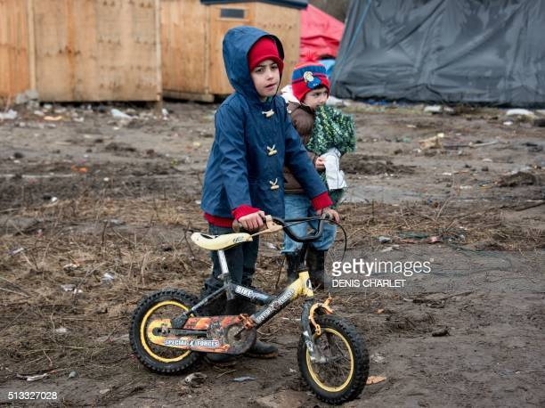Migrant children play in the southern part of the socalled 'Jungle' migrant camp on March 2 2016 in Calais northern France French demolition workers...