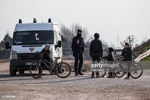 Migrant children talk with a police officer near a cleared area that used to be part of the 'jungle' camp on February 27 2016 in Calais France The...
