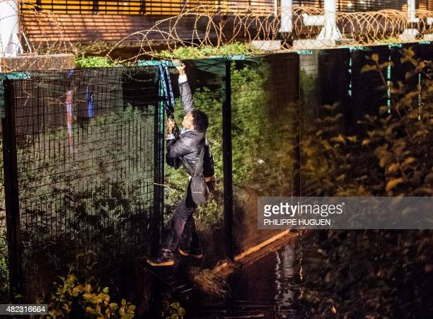 A migrant climbs a security fence of a Eurotunnel terminal in Coquelles near Calais northern France on July 30 2015 One man died on July 29 in a...
