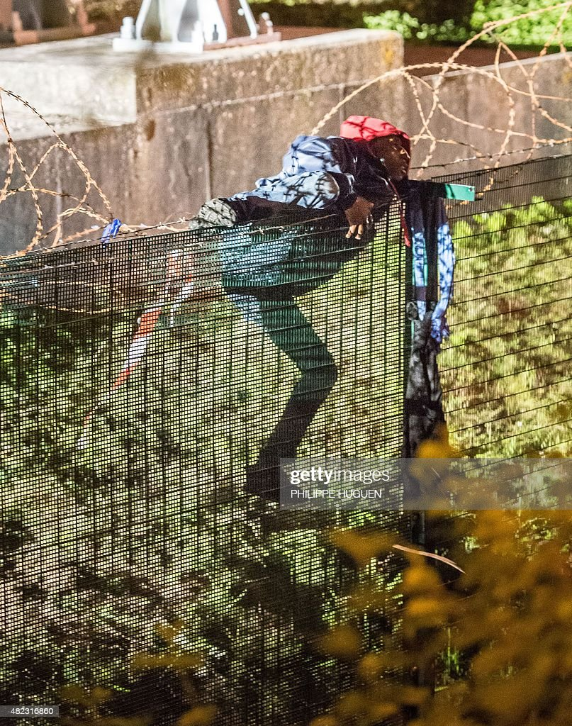 A migrant climbs a security fence of a Eurotunnel terminal in Coquelles near Calais, northern France, on late July 29, 2015. One man died on July 29 in a desperate attempt to reach England via the Channel Tunnel as overwhelmed authorities fought off hundreds of migrants, prompting France to beef up its police presence.