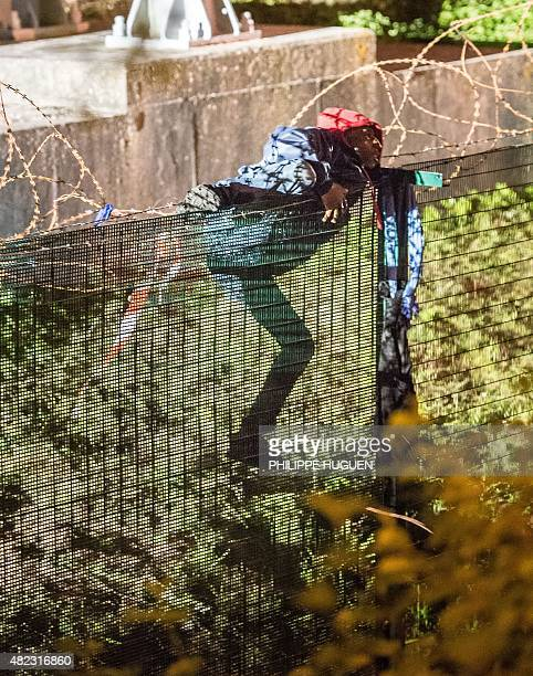 A migrant climbs a security fence of a Eurotunnel terminal in Coquelles near Calais northern France on late July 29 2015 One man died on July 29 in a...