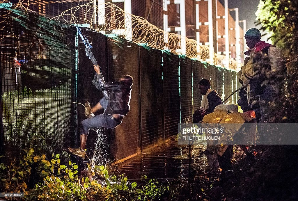 A migrant climbs a security fence of a Eurotunnel terminal in Coquelles near Calais, northern France, on July 30, 2015. One man died on July 29 in a desperate attempt to reach England via the Channel Tunnel as overwhelmed authorities fought off hundreds of migrants, prompting France to beef up its police presence.