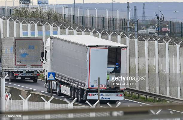 TOPSHOT A migrant climbs into the back of lorries bound for Britain while traffic is stopped upon waiting to board shuttles at the entrance to the...