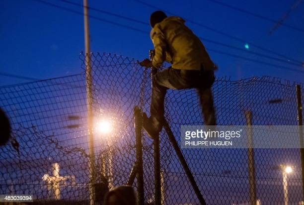 A migrant climbs over a fence into the Channel Tunnel site in Frethun northern France on August 5 2015 The European Commission offered August 4 to...