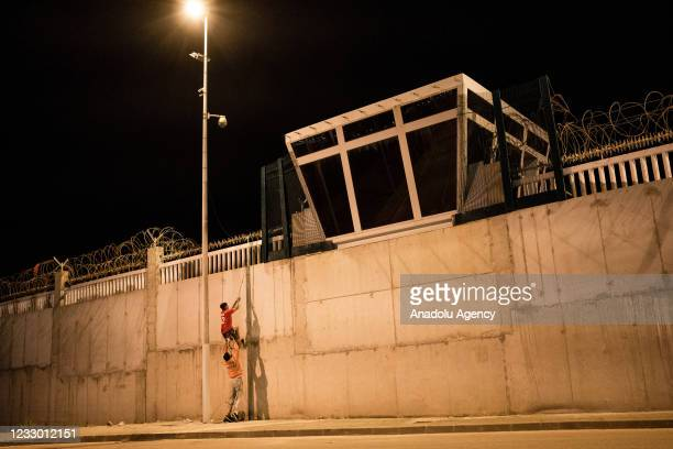Migrant climbs the border wall by throwing a rope with the help of another migrant in Spanish enclave of Ceuta on May 21, 2021. Eight thousand...