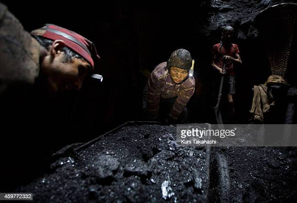 Migrant coal miners from Nepal carry coal at a mine hole in Jaintia Hills Meghalaya in India on April 30 2014 Indian government announced in...